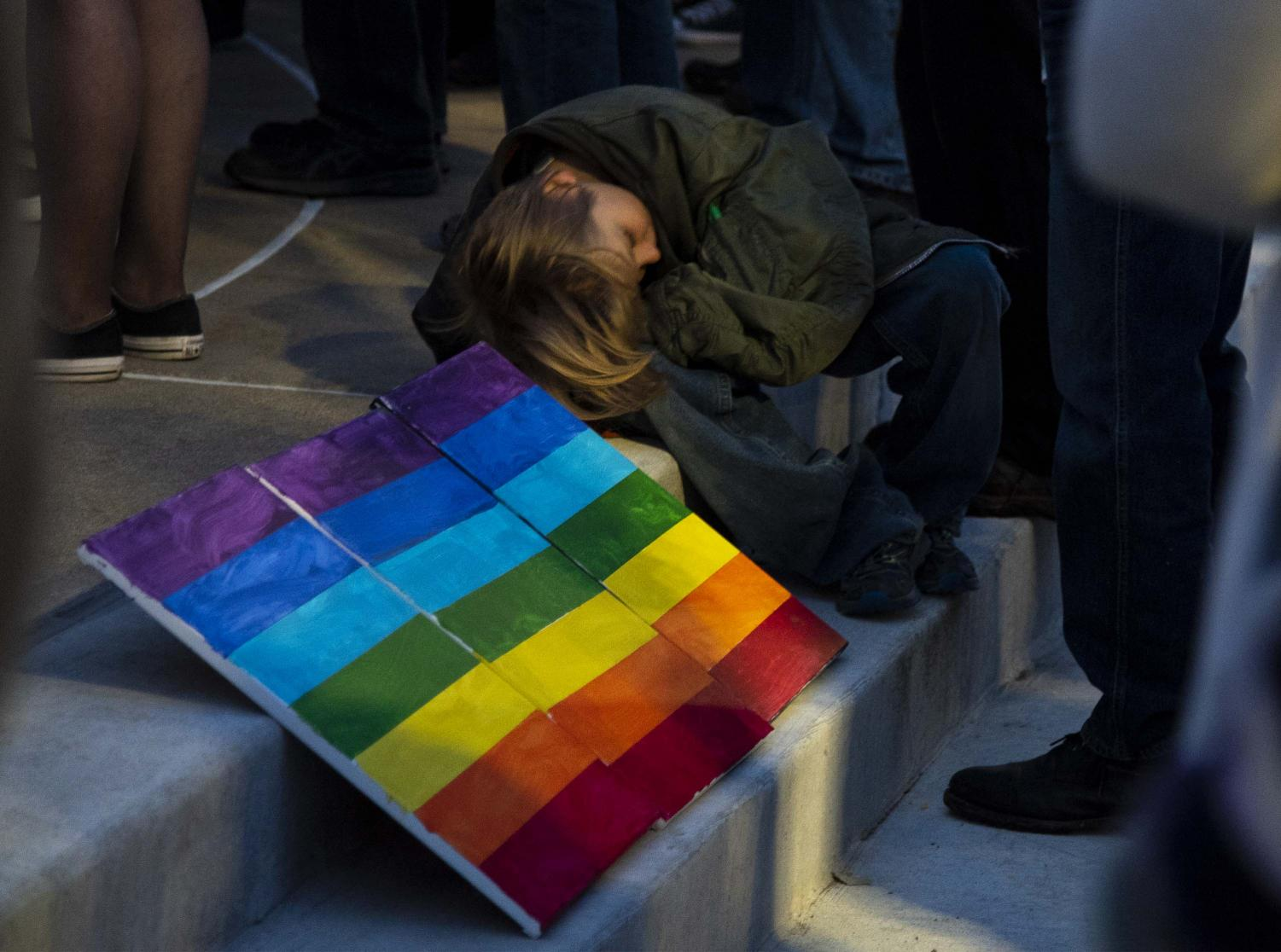 A+child+laying+next+to+a+three-panel+LGBTQ%2B+rainbow+sign+on+the+steps+of+the+Carbondale+City+Hall+during+the+City+Assembly+to+Shut+Down+Trump+event%2C+Tuesday%2C+Oct.+23%2C+2018.+%28Allie+Tiller+%7C+%40allietiller_de%29%28Allie+Tiller+%7C+%40allietiller_de%29