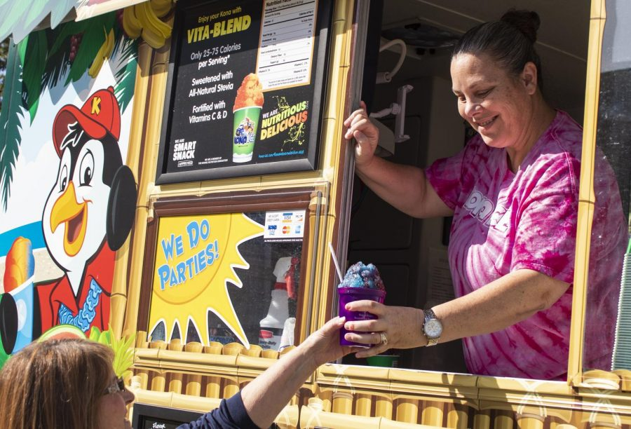 """Kelly Buck hands Kelly Lyndonberg a snowcone, Wednesday, Oct. 24, 2018, outside Morris Library. """"We donate all the money to the breast cancer awareness organization here,"""" says Buck. (Nick Knappenburger 