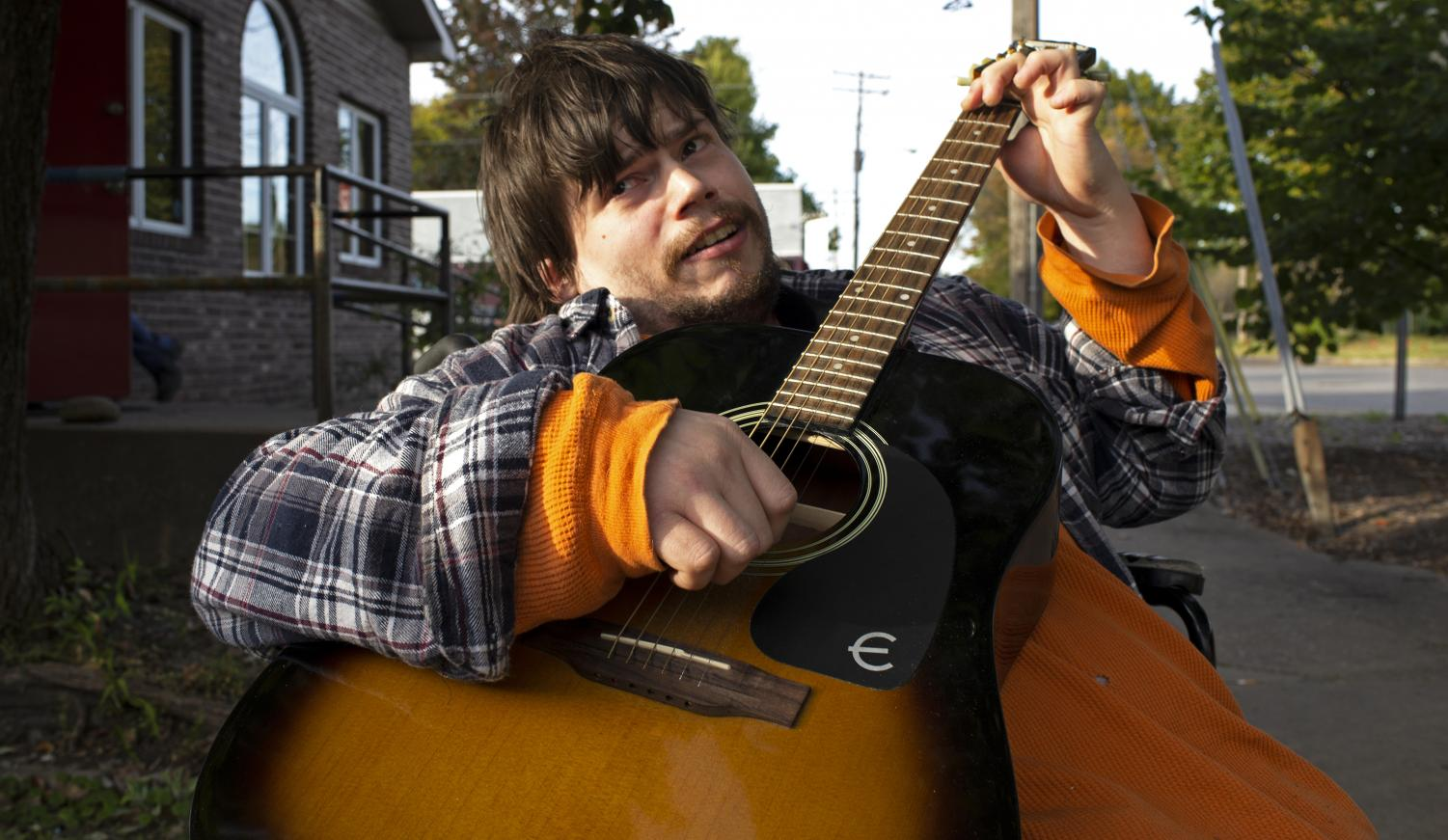 Joey Odum, 29, of Marion sings and strums an original song outside of WDBX 91.1 FM Community Radio Station on Oct. 24, 2018.