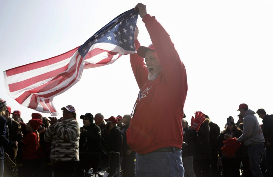 Kevin Sauls, from Ridgway, Illinois waves an American flag while waiting in line for the Trump rally in Murphysboro, Saturday, Oct. 27, 2018. God put [Trump] here to save our country, Sauls said.