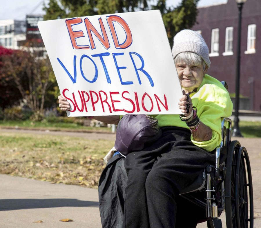 Ann DeHorn, 69, of Carbondale holds up an End Voter Suppression sign along side East Main St. in Carbondale for the voting rights vigil, Saturday, Nov. 3, 2018 put on by the Peace Coalition of Southern Illinois. (Allie Tiller | @allietiller_de)