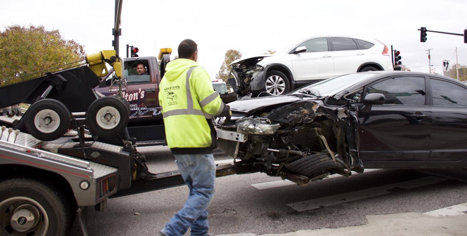 Tow truck drivers move vehicles involved in a collision Monday, Nov. 5, 2018, at the intersection of S. Illinois Avenue and Mill Street in Carbondale. (Joey Sears | @Joey_Sears10)