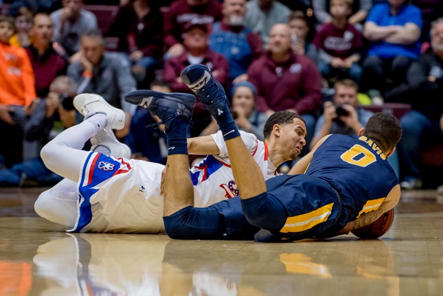 Southern Illinois junior guard Eric McGill dives to get the ball from Murray State Racers forward Mike Davis on Wednesday, December 12, 2018 during the first half of the Salukis matchup against the Murray State Racers.