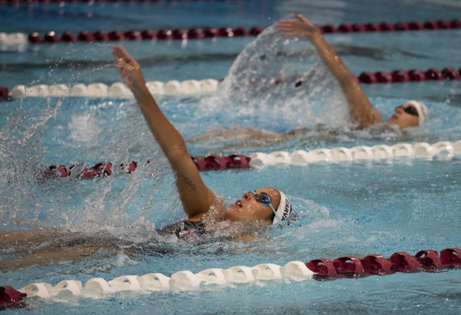 Junior Juliana Carvalho, of Rio de Janeiro, Brazil, studying art, competes in the 100 yard backstroke alongside a competitor on Saturday, Jan. 19, 2019 at the SIU vs. Arkansas-Little Rock swim meet  in the Dr. Edward J. Shea Auditorium. Carvalho placed fourth with a time of 1:01.61.