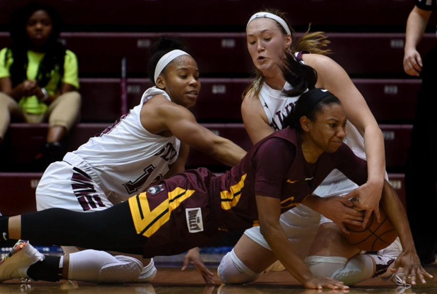 Southern Illinois Saluki guard Kristen Nelson and Forward Abby Brockmeyer grapple for the ball on Sunday, Jan. 27, 2019, during the Southern Illinois Salukis' 74-63 win over the Loyola Ramblers at SIU Arena.