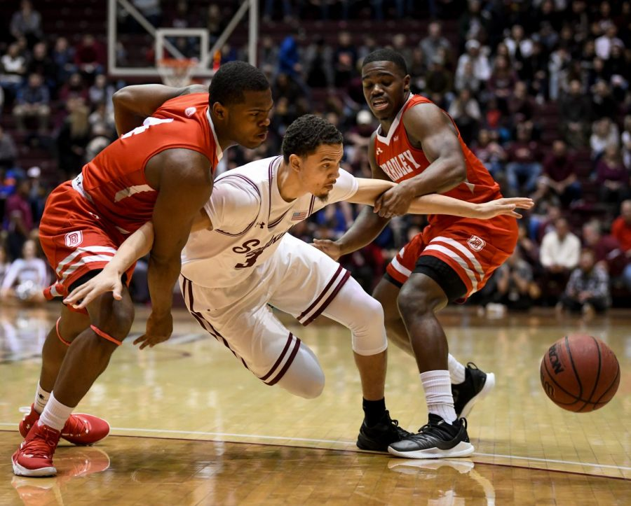 Southern Illinois Salukis guard Marcus Bartley attempts to go for a loose ball while being held back on Sunday, Jan. 20, 2019, during the Bradley Braves 57-54 win over the Southern Illinois Salukis at SIU Arena.