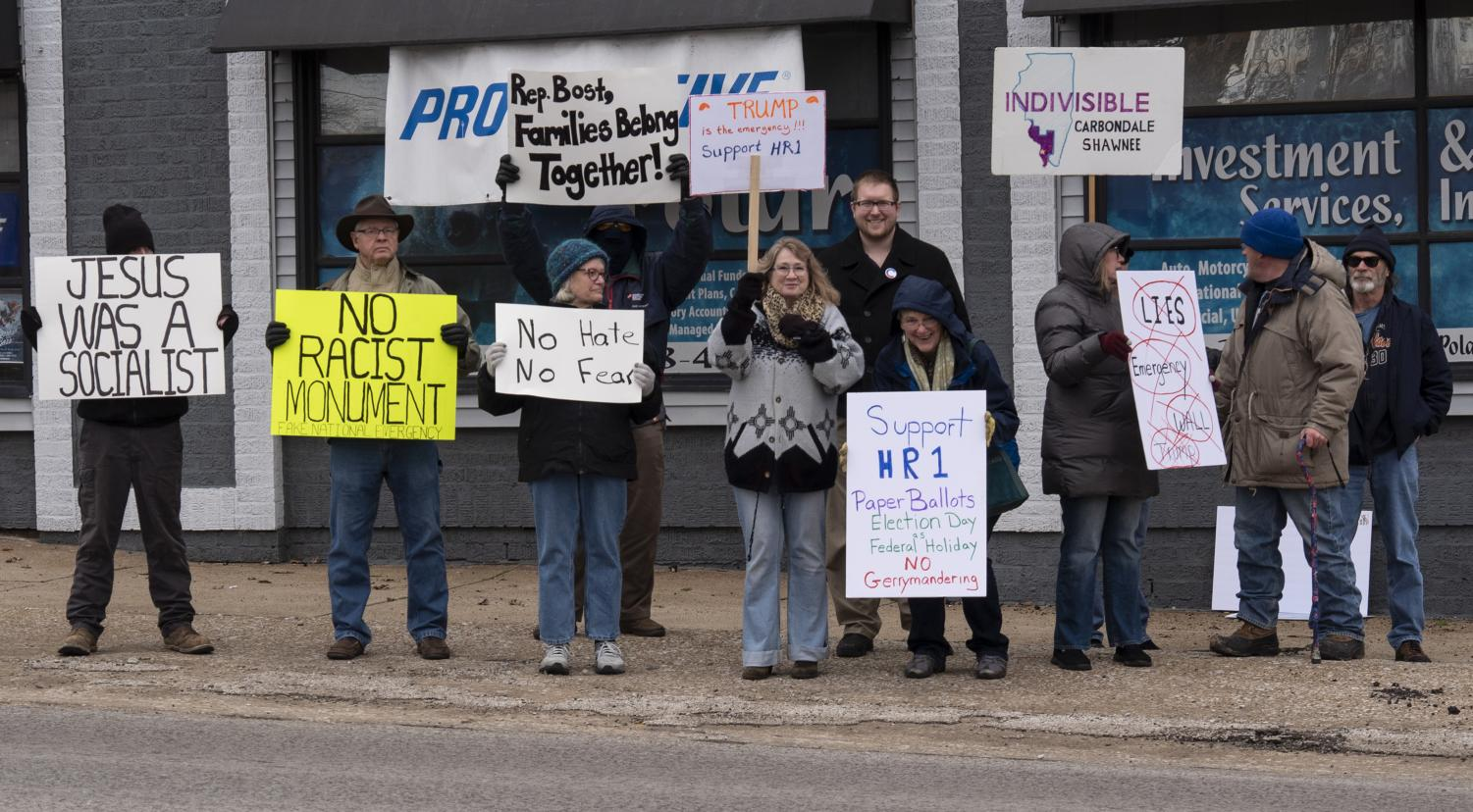 Protestors stand alongside Carbondale mayoral candidate Nathan Colombo on Monday, Feb. 18, 2019 outside Carbondale's Hunter Building. The group protested President Donald Trump's recent declaration of a national emergency on the Mexican border.