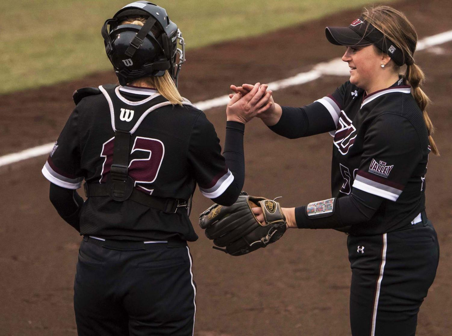 Saluki+catcher+Shelby+Hodo+and+pitcher+Claire+Miller+high+five+on+Friday%2C+Feb.+22%2C+2019+during+the+Salukis+3-0+win+against+Ohio+University+at+Charlotte+West+Stadium.+