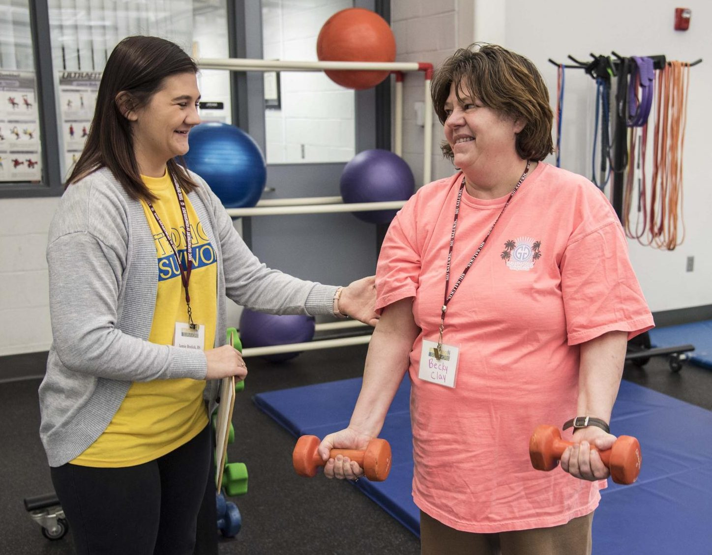 Jamie Brolick assists Strong Survivor participant, Becky Clay, as she lifts weights in the Aerobics and Weight Training Center on Tuesday, Feb. 19, 2019 at John A. Logan. Brolick actively volunteers in the program in order to help cancer survivors regain their strength.
