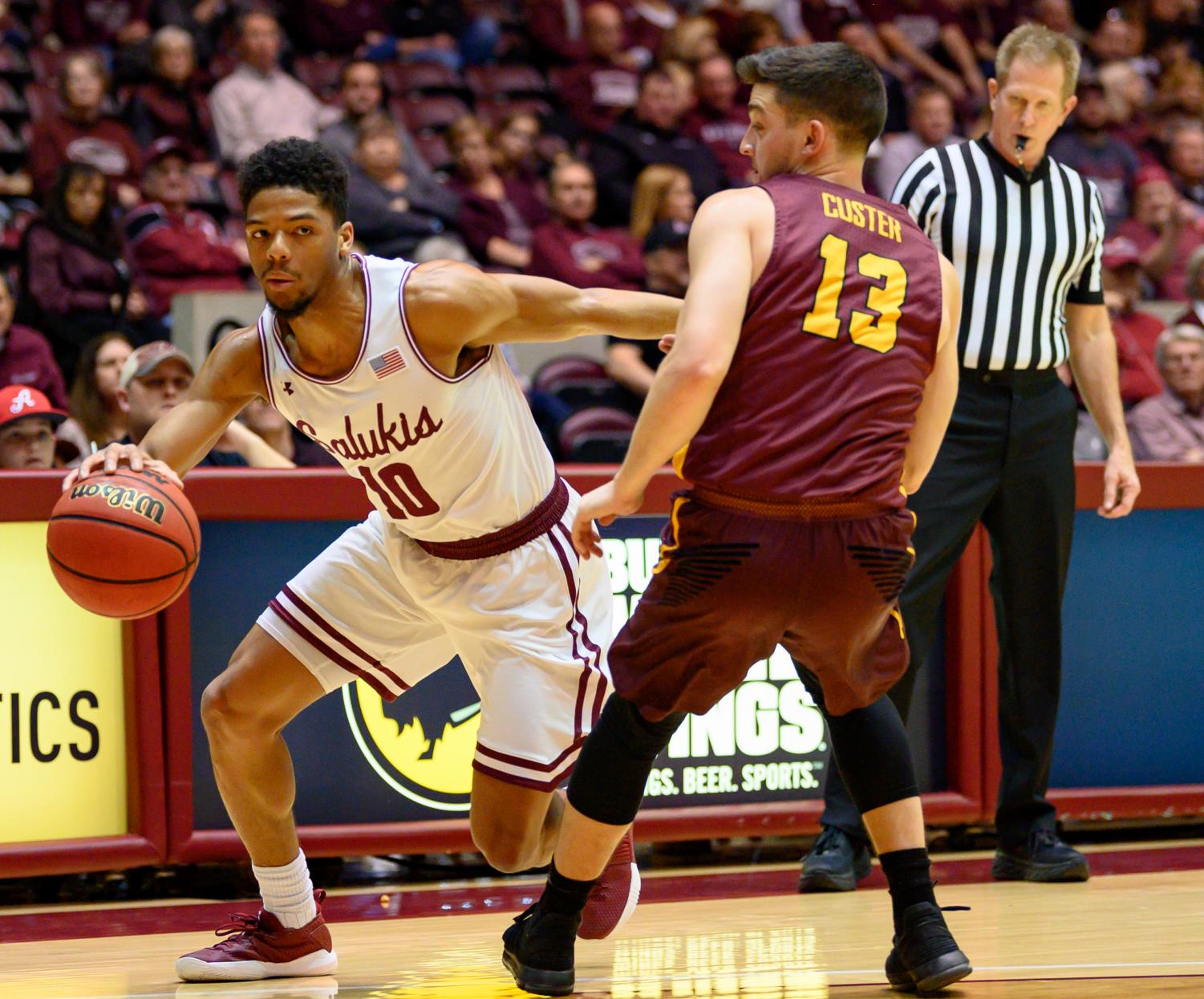 Southern Illinois Salukis guard Aaron Cook attempts to get around Loyola Ramblers guard Clayton Custer on Sunday, Feb. 24, 2019, during a matchup between the Southern Illinois Salukis and the Loyola Ramblers at SIU Arena.