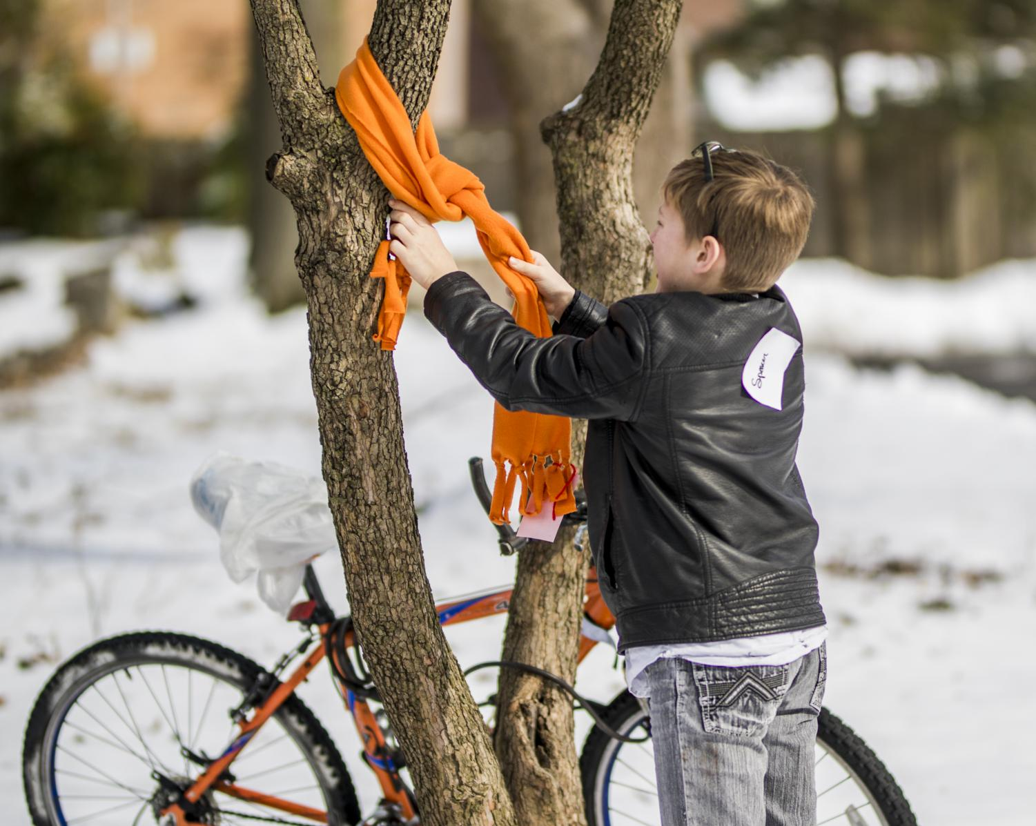 Ten-year-old Spencer Crotser, of Cambria, hangs a scarf on a tree, Saturday, Feb. 16, 2019, during the SIU Social Work Interns warming event at the Public Library.