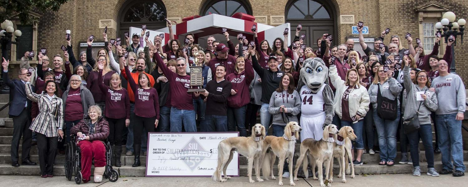 Attendees gather for a group photo during the BEER scholarship trophy presentation on Friday, March 29, 2019 during the SIU Day of Giving outside Shryock Auditorium.