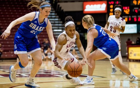 Southern Illinois Salukis guard Brittney Patrick attempts to drive the ball past Drake Bulldogs guard Sammie Bachrodt and Drake Bulldogs guard Hannah Fuller on Friday, March 1, 2019, during a matchup between the Southern Illinois Salukis and the Drake Bulldogs at SIU Arena.