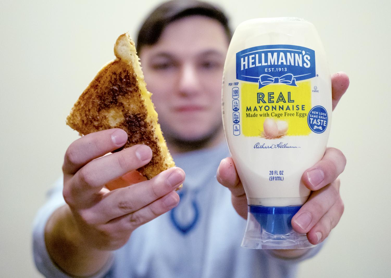 Jacob Lorenz holds up a grilled cheese sandwich and a jar of Hellman's Mayonnaise on April 4, 2019, in his apartment at the Saluki Pointe.