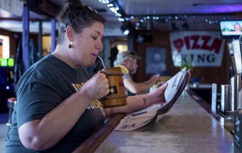 Lisa Pangburn-Fenton, of De Soto, sips her drink while she reads the newspaper on Tuesday, April 23, 2019, at PK's in Carbondale.