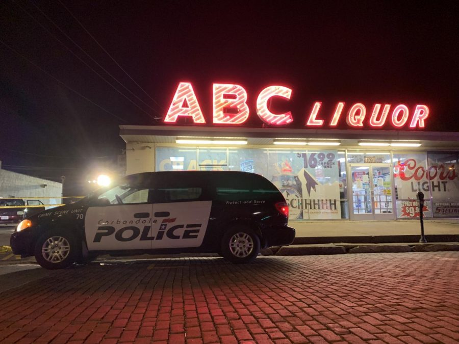 A Carbondale crime scene squad car sits outside of ABC Liquor on Friday, April 12, 2019, after a shooting outside of the store and Tres Hombres Mexican Restaurant and Bar.