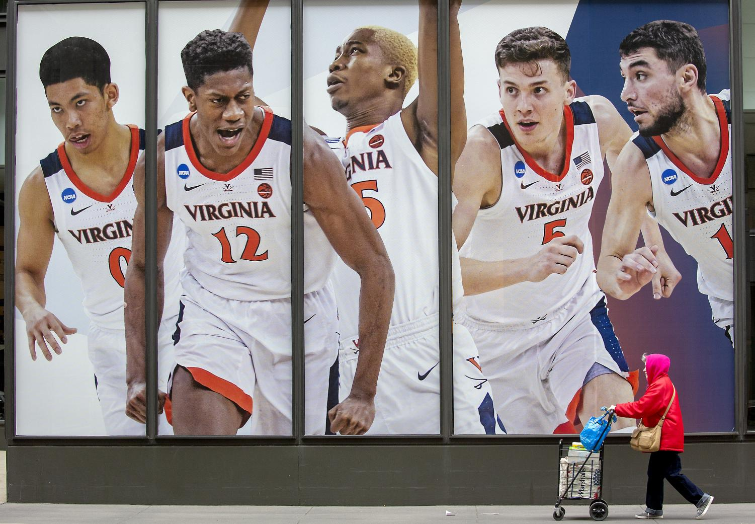 Pedestrians made their way by giant-sized posters of Final Four players near 7th Street and Marquette Avenue on the windows of the IDS Center, Monday, April 1, 2019 in Minneapolis, Minn.