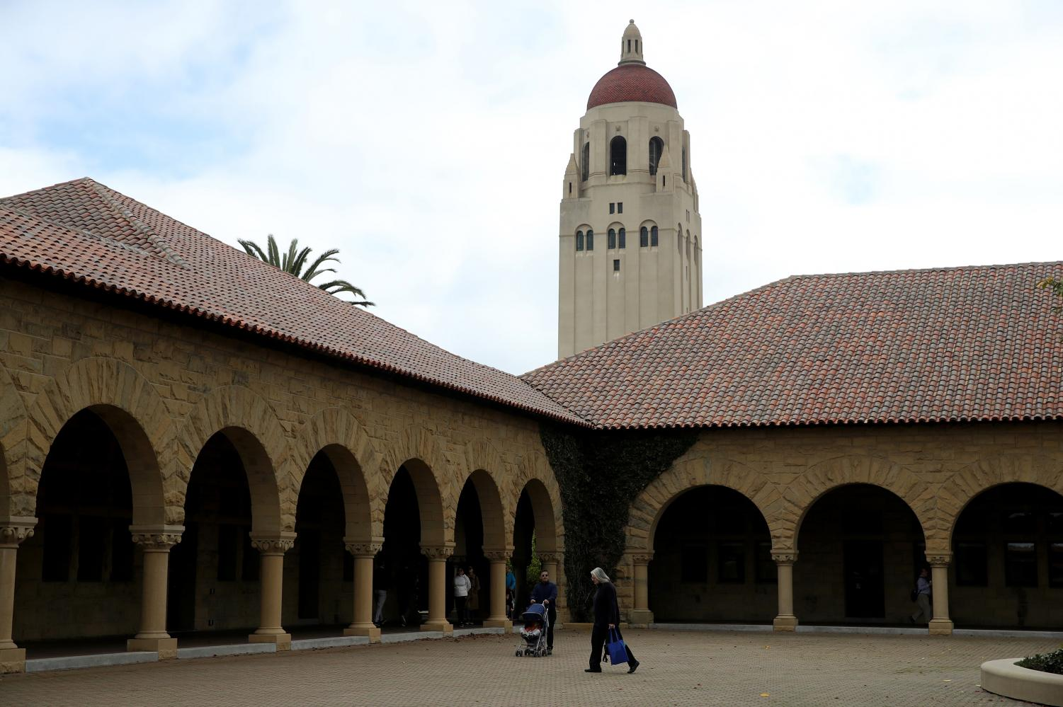 People walk by Hoover Tower on the Stanford University campus on March 12, 2019 in Stanford, Calif.