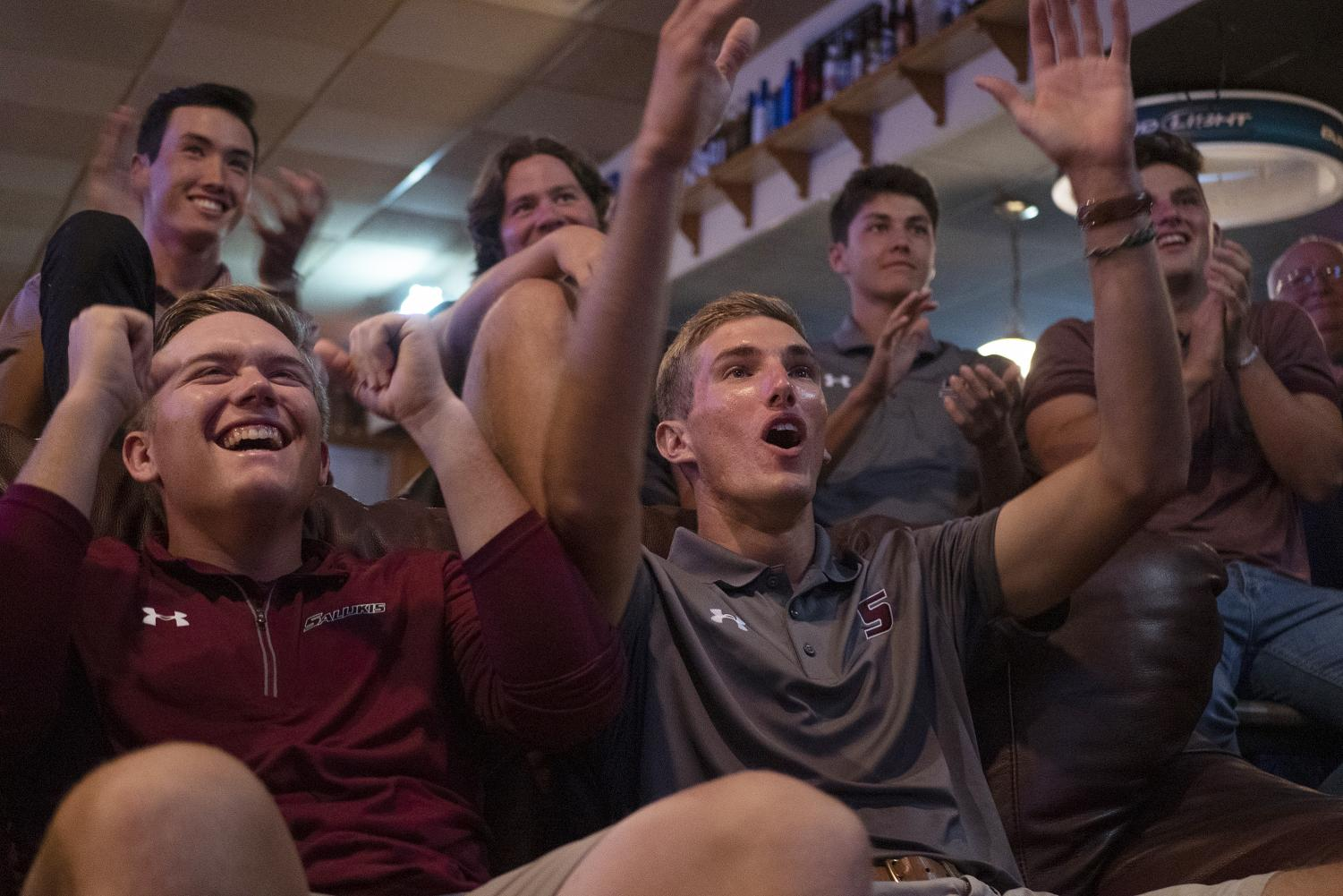 "Seniors Peyton Wilhoit, of Searcy, Ariz., and Hunter York, of Decatur, react to their selection alongside the rest of the golf team on Wednesday, May 1, 2019, in Copper Dragon in Carbondale. York said, ""It's Louisville so it is convenient and close, it's a great place [...] we're super excited to get there and play in Nationals."""
