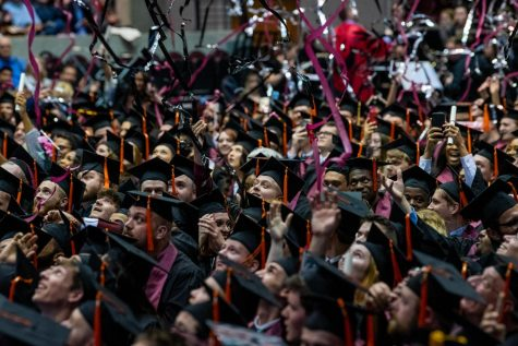 Graduated students react as confetti falls down on them on Saturday, May 11, 2019 during the 2019 commencement inside the SIU Arena.