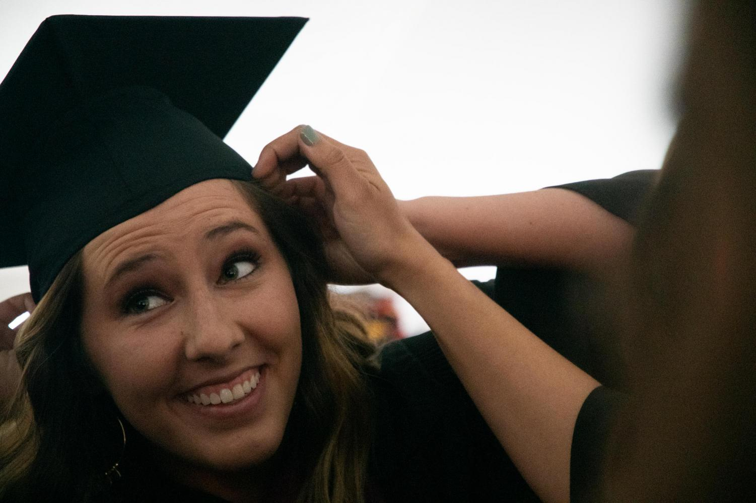 Bailey+Nippe%2C+a+senior+graduating+with+a+degree+in++dental+hygiene+gets+help+from+friends+to+adjust+her+hat+on+Saturday%2C+May+11%2C+2019+during+the+2019+commencement+inside+the+SIU+Arena.+