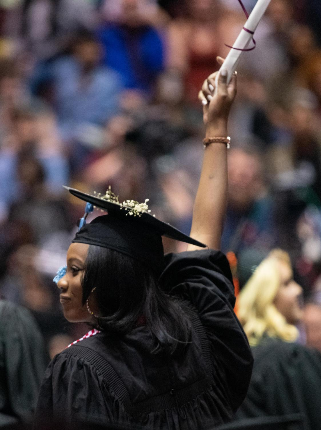 Alliyah+Bridges+holds+up+her+diploma+on+Saturday%2C+May+11%2C+2019+during+the+2019+commencement+inside+the+SIU+Arena.+Trotter+graduated+with+a+bachelors+in+cinema+and+photography.