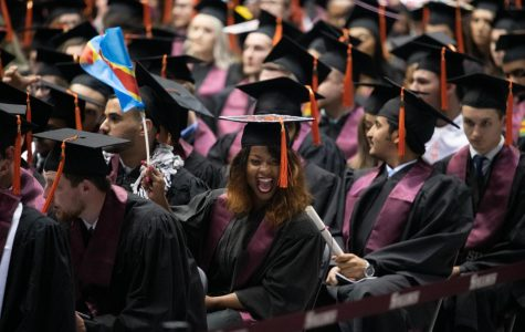 Marie-Esperanoce Namage Baseleba waves the Democratic Republic of Congo's flag to her family on Saturday, May 11, 2019 during the 2019 commencement inside the SIU Arena.  Baseleba, from the Democratic Republic of Congo, received her degree in Computer Engineering.
