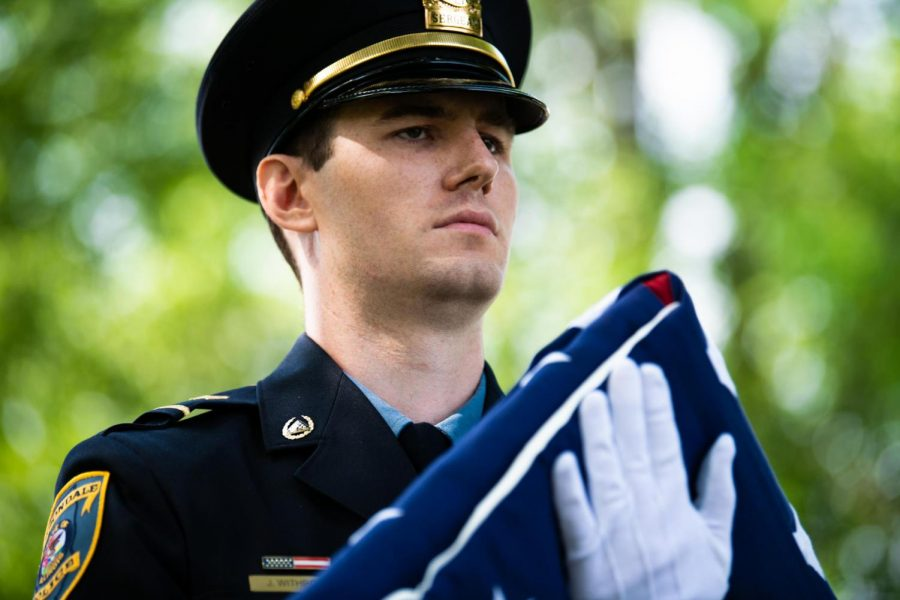 A member of the Carbondale Fire and Police Honor Guard carries the American flag on Monday, May 27, 2019 during the Carbondale Memorial Day Service at Woodlawn Cemetery in Carbondale, Illinois.