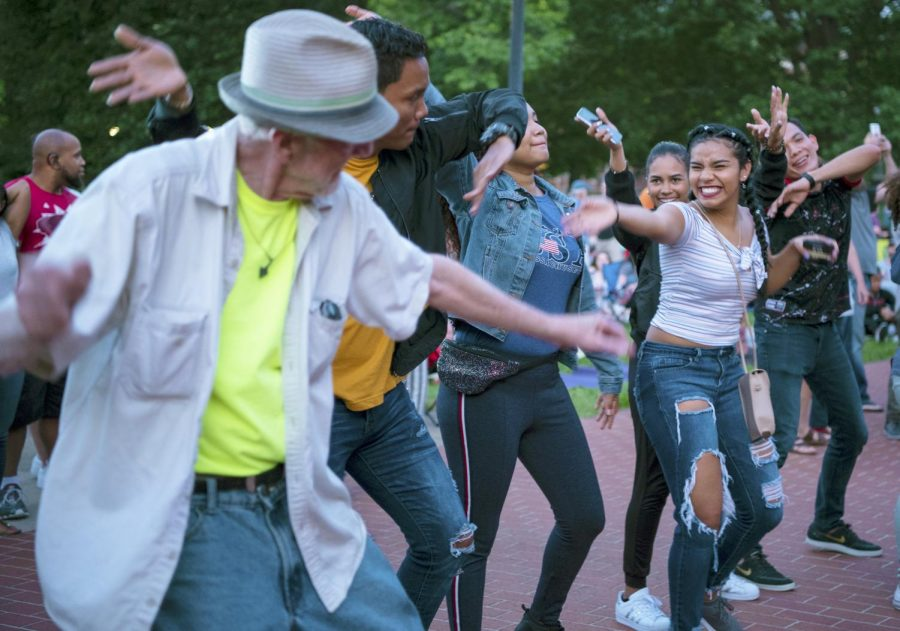 Concertgoers dance and swing their arms together on Thursday, June 13, 2019, at the Sunset Concert outside of SIU's Shryock Auditorium. Donovan Keith a singer from Austin, Texas sang a soul and rock n' roll during the concert.
