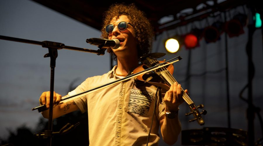 Sam Craft sings and plays the violin on Thursday, June 27, 2019, at the corner of Washington St. & RT. 13. Sweet Crude is a Louisiana drum pop band that performs indie rock music.