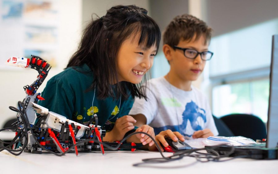 Aurora Cui smiles while working with Jeronimo Gonzalez on their scorpion robot