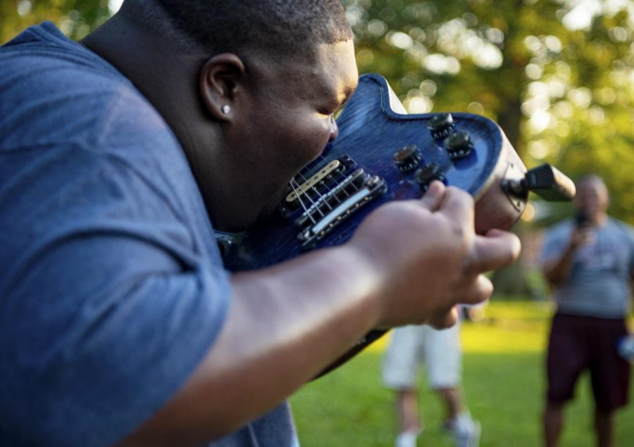 """Christone """"Kingfish"""" Ingram plays a guitar solo with his teeth on Thursday, July 18, 2019, during the Sunset Concert at Carbondale's Lenus Turley Ingram is from Clarksdale, Mississippi and pulls inspiration for his music across genres."""