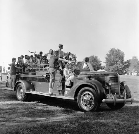 "People in an old car, with the name Carbondale written on it, celebrating the Fourth of July. Photo courtesy of Morris Library Special Collections Research center, collection of ""Neighboring Celebration,"" from July 4, 1968."