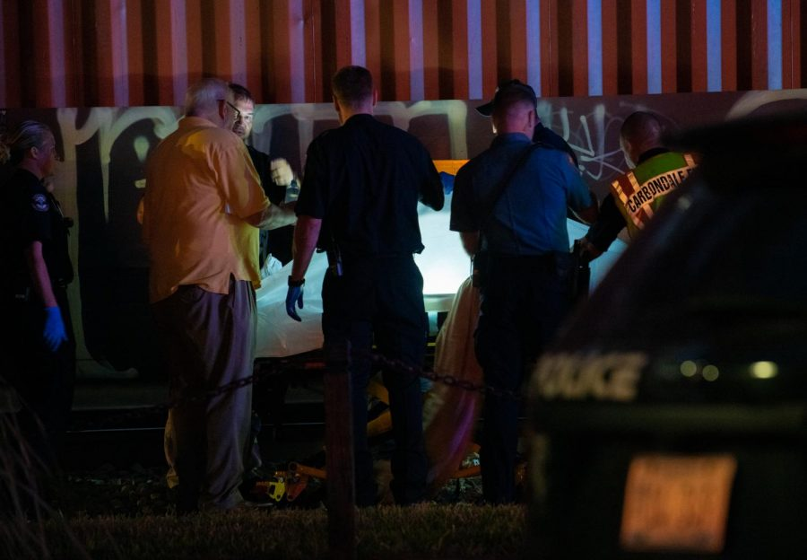 Carbondale Police and Fire look inside a body bag on Monday, Sept. 2, 2019 at the railroad crossing at Route 13 and Main Street in Carbondale. At approximately 6 p.m. Carbondale Police responded to the railroad crossing in connection to an individual being struck by a train.