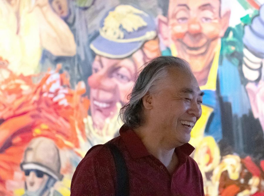 Yingxue Zuo standing next to one of his paintings during his exhibit at the SIU University Museum on Saturday, Aug. 31, 2019