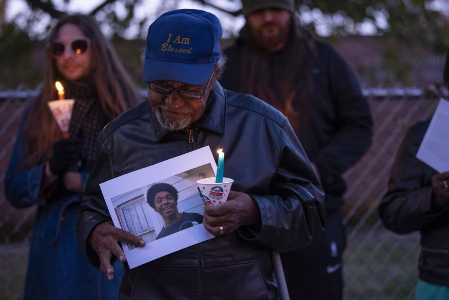 Rodney Cavitt, of Carbondale, holds a candle and a photo of Xe'Quan Campbell on Tuesday, Nov. 5, 2019, alongside Freeman Street in Carbondale at the Vigil for Xe'Quan Campbell and Keon Cooper.