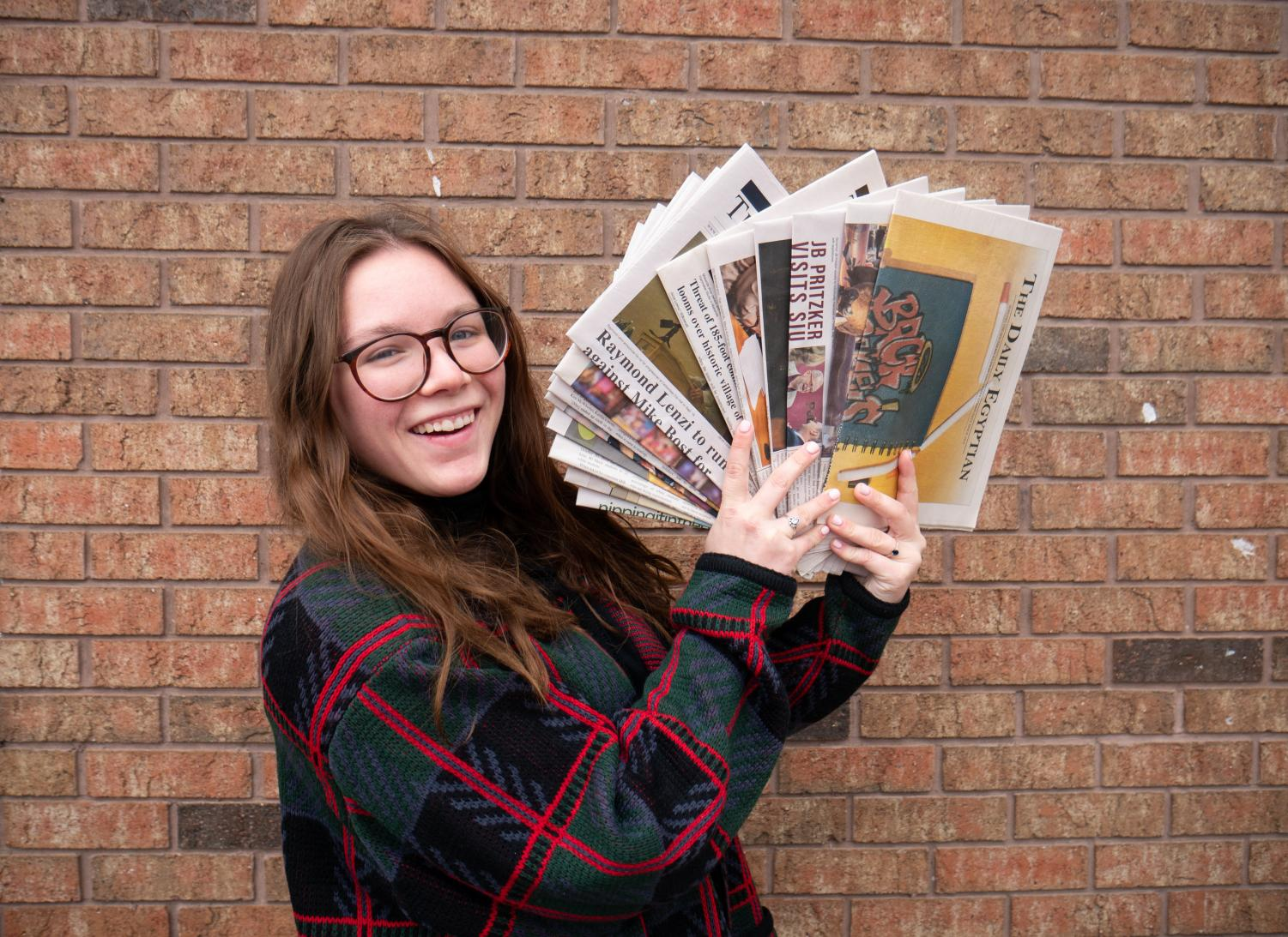 Editor-in-chief Emily Cooper holds up copies of the Daily Egyptian on Dec. 10, 2019.