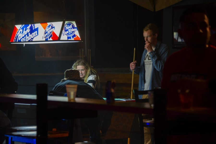Justin Crebo of Bolingbrook, Gabrielle Canlas of Naperville and Nick Defly of Naperville play pool at Hangar 9 early Sunday morning, Jan. 26.