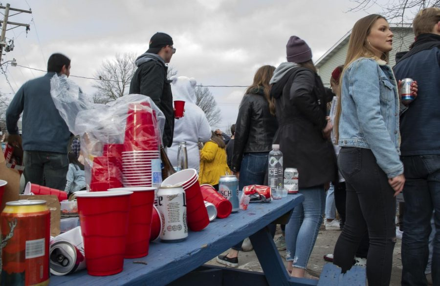 Beer cans and plastic cups rest on a picnic table as partygoers mingle at a Polar Bear gathering Saturday, Jan. 25 at the Beta Chi house on Cherry St in Carbondale.