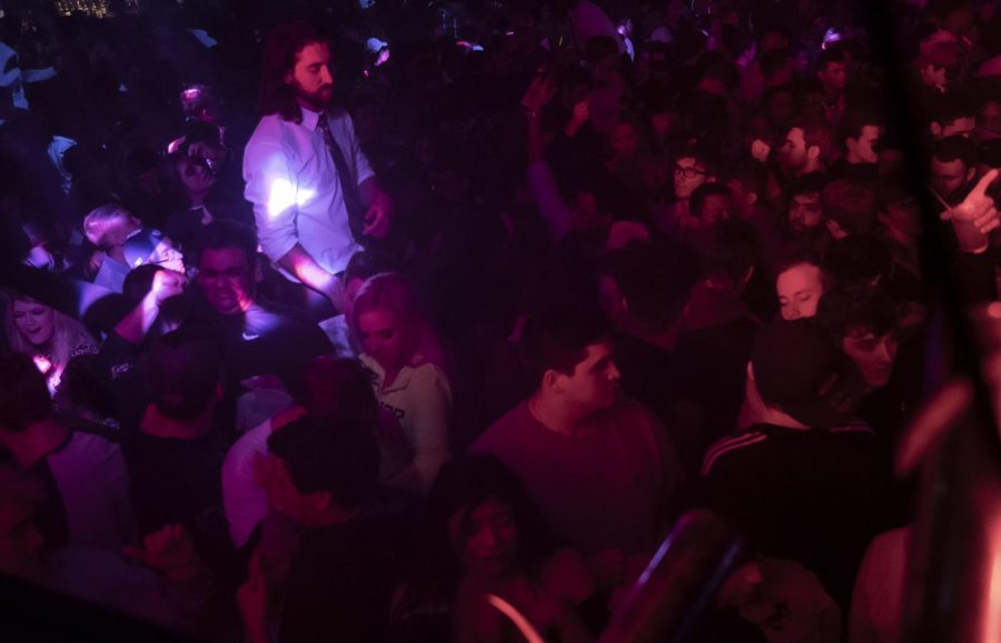 A Levels employee sits over the crowd while patrons dance at Levels'