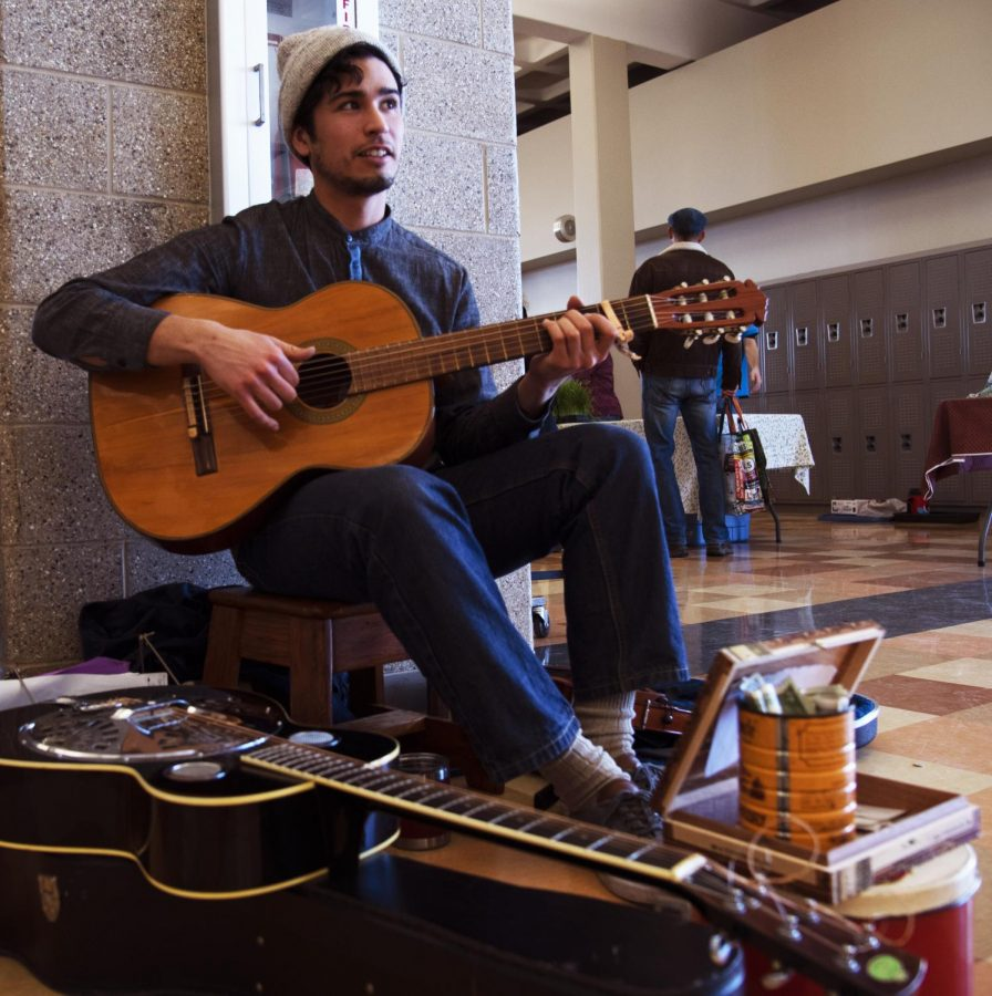 Stefan Santiago, from Makanda Illinois, sings and plays guitar for the crowd attending the Carbondale Community Farmers Market. The market was help at Carbondale Community High School on Saturday, February 29, 2020.