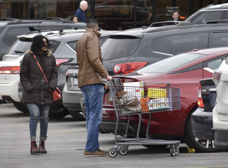 A+couple+unloads+their+purchases+from+Binny%E2%80%99s+Beverage+Depot+into+their+sedan+March+20+in+Lincolnwood%2C+Illinois.+Despite+closing+many+businesses%2C+Governor+Pritzker+announced+that+liquor+stores+and+marijuana+dispensaries+are+deemed+%E2%80%9Cessential+businesses%2C%22+meaning+they+will+stay+open+through+the+stay-at-home+order.