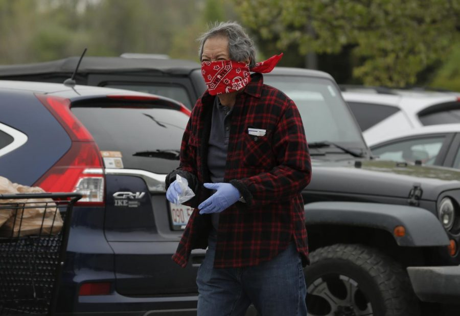 A shopper visits Kroger supermarket wearing a bandana on his face and rubber gloves, Carbondale, IL, Saturday, April 4, 2020.  Some shoppers opted to wear homemade medical masks, bandanas, or some other improvised facial covering to help protect against the Covid-19 pandemic.     (Angel Chevrestt, 646.314.3206)