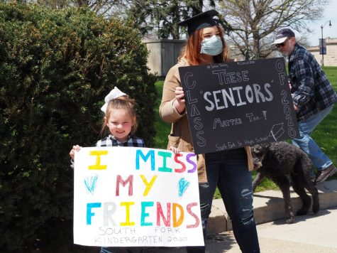 Jayden Brest, a senior at South Fork Senior High School, holds a sign next to her sister, who is in kindergarten, at the