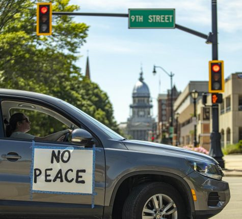 A protestor drives with a sign past the  Illinois capitol building, as part of the Solidarity Procession put on by the Black Lives Matter SPI in response to the country-wide protests following the death of George Floyd.