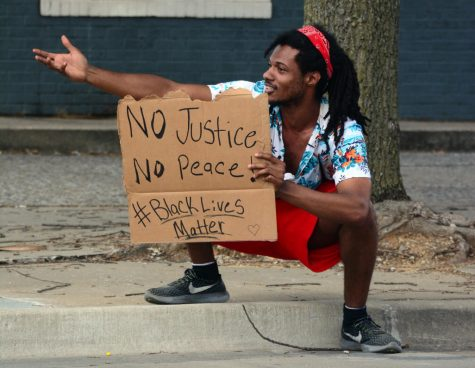 Zyon, 24, captures the attention of passing cars during a Black Lives Matter protest at the corner of South Illinois Avenue and West College Street, Wednesday, June 3, 2020, in Carbondale, ILL.