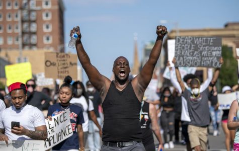 A man puts both hands in the air as he joins in with protestors' chants of 'hands up don't shoot!' on Monday, Jun. 1, 2020 in Springfield, IL.