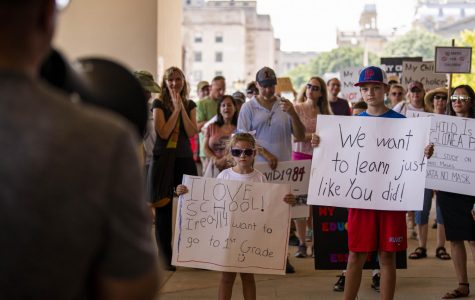 Kids hold signs at the Illinois State Board of Education (ISBE) building as protestors speak about the ISBE's mask guidelines for the schools for the fall semester on Saturday, July 25, 2020 in Springfield, IL.