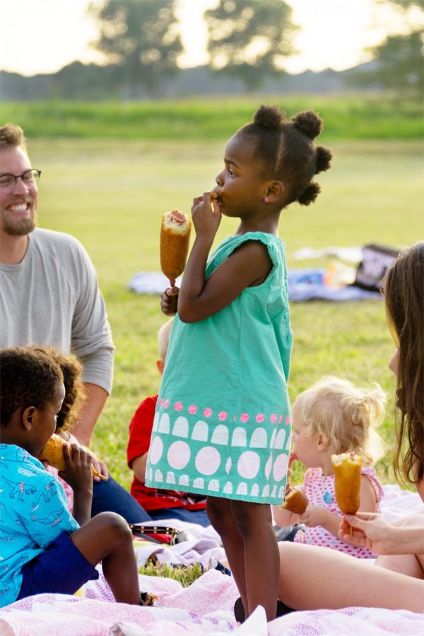 "Ruby Todd, 4, enjoying a corndog with her family and friends while waiting for ""Movies on the Lawn"" to start at the Food Truck Fridays in Marion, Ill., August 22, 2020. Food Truck Fridays are happening every Friday at The Pavilion of The City of Marion, from 11:00 a.m. to 8:00 p.m. According to the administrative assistant, Jeff Bird, there will be live music, food trucks, and a different movie every week."