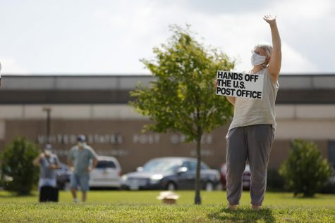"Rose Weisburd, 55, of Carbondale, IL, waves at passing motorists that honked their car horn in support of Weisburd and a group of about 19 other protesters outside the main post office in Carbondale.  The group of protestors gathered in solidarity with a nationwide call for a #SaveThePostOfficeSaturday rally on Saturday, August 22 ,2020. MoveOn, the NAACP, WorkingFamiliesParty, Indivisible and other national organizations announced the nationwide effort to show up at post offices across the country at 11Am on Saturday, August 22, ""to save the post office from Trump and declare that Postmaster General Louis DeJoy must resign.""  Angel Chevrestt // @sobrofotos"